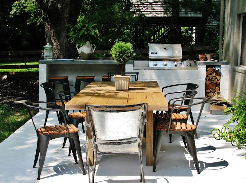 Área gourmet rústica simples com mesa de jantar de madeira.