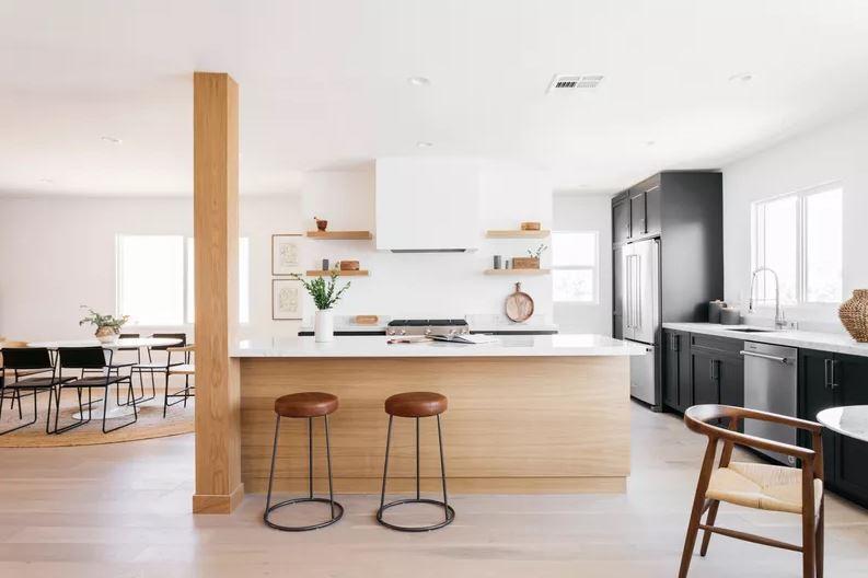 Cozinha aberta com piso, ilha e viga de madeira natural clara.