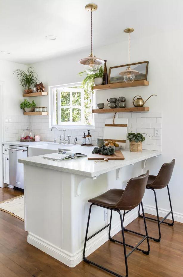Cozinha pequena aberta com parede, ilha e janela branca.