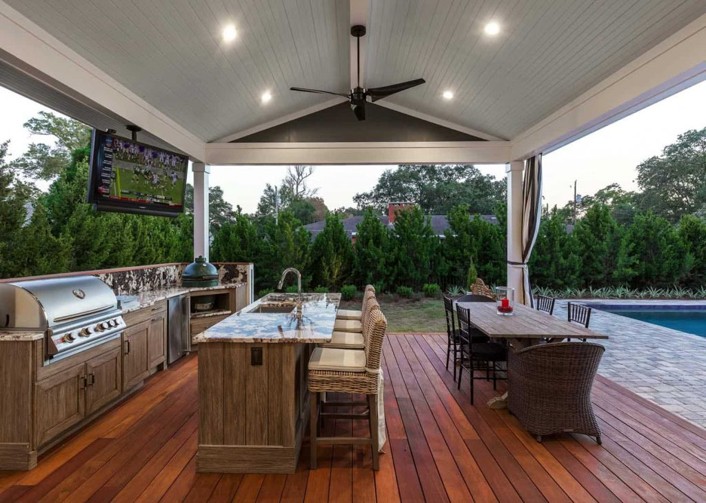Ampla área externa rústica com espaço gourmet e deck de madeira.
