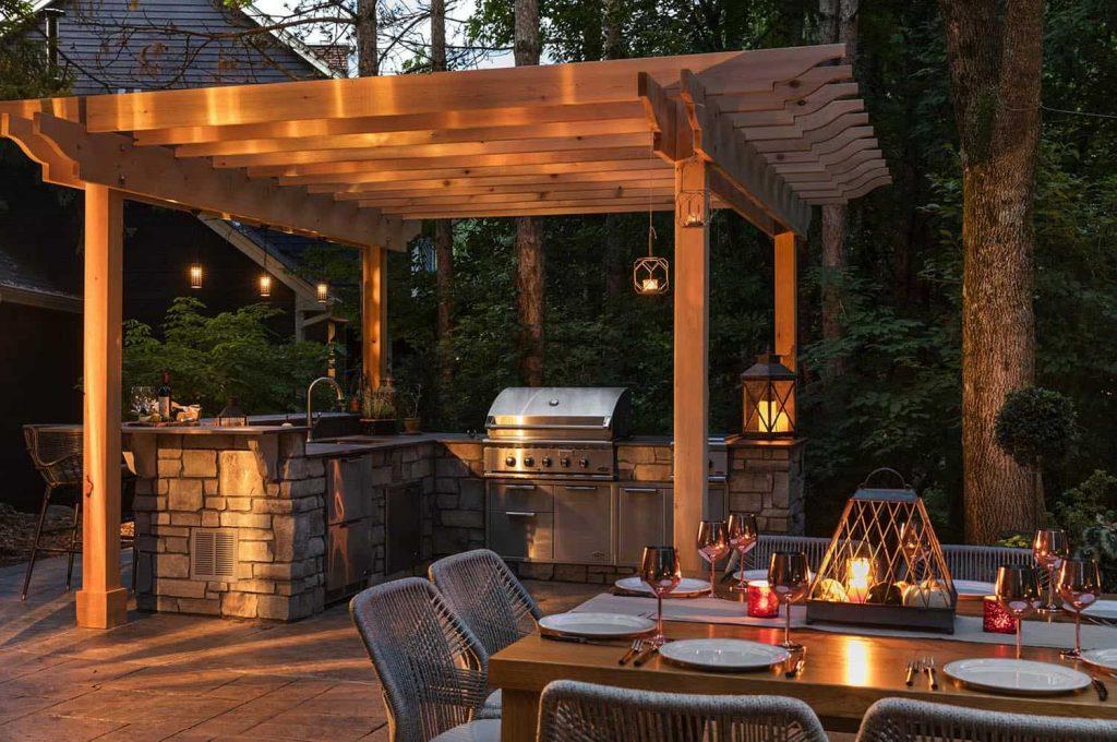 Cozinha gourmet externa com pergolado de madeira.