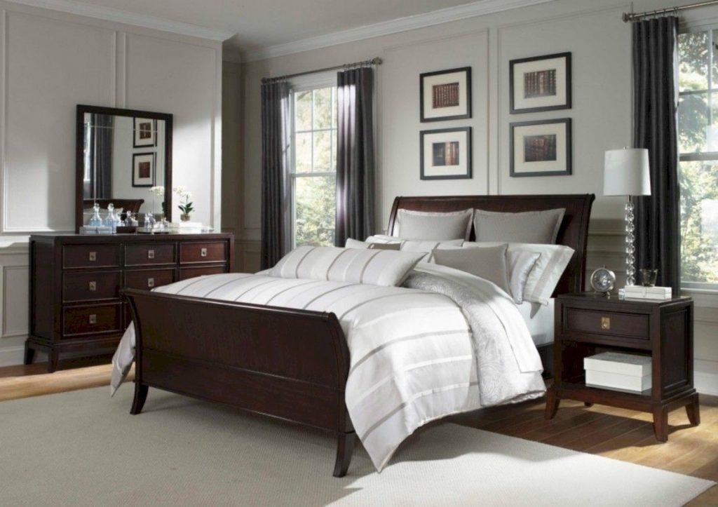 Quarto com cama, cômoda e mesa de cabeceira em cores de madeira escura.