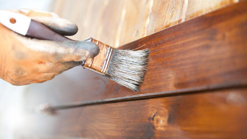 Mão segurando pincel passando verniz marrom em madeira clara.