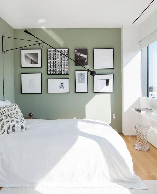 Quarto com parede verde e piso de madeira.
