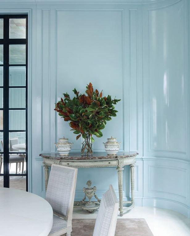 Parede com boiserie de madeira pintada em tinta de laca azul clara.