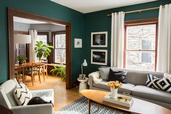 Sala com paredes verde azuladas e móveis de madeira.