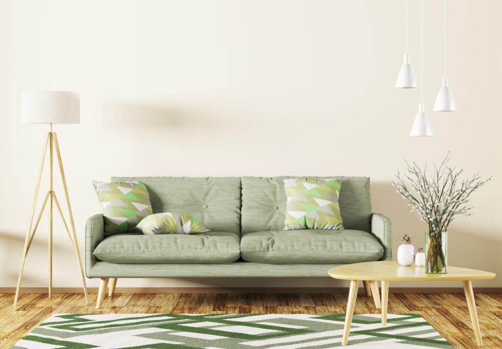 Sala com sofá e tapete verdes e assoalho de madeira.